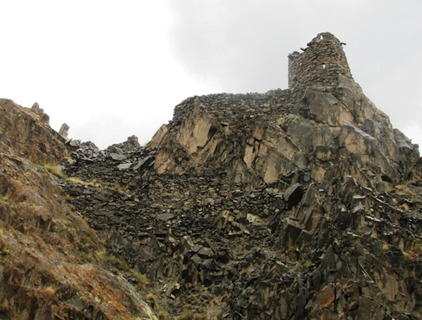 Fig. 4: One portion of Stok Mon Khar. Portions of this extensive facility may have been developed after its original foundation date, as exhibited in alternative modes of construction. Once we have Quentin's final report we will know better. Note the staggered ramparts in the concave central slope, a defensive bulwark regularly encountered in the archaic fastholds of Upper Tibet. Also note the loopholes in the tall summit structure on the upper right hand side of the image. Such apertures are uncommon in all-stone corbelled citadel architecture of Upper Tibet, as is its circular plan. Photograph by Quentin Devers