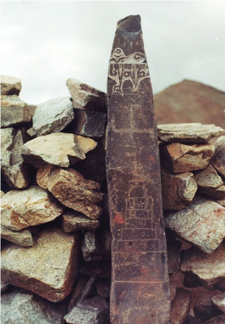 Fig. 14. One of a number of pillars in northwestern Tibet integrated into a corral. Presumably there was once an enclosure as well. This particular specimen was engraved with a swastika and two primitive shrines at different times long ago. In contrast, the letters Om' ma ni at the top of the stele were carved at a much later date, as indicated by the relative level of erosion exhibited by the various carvings