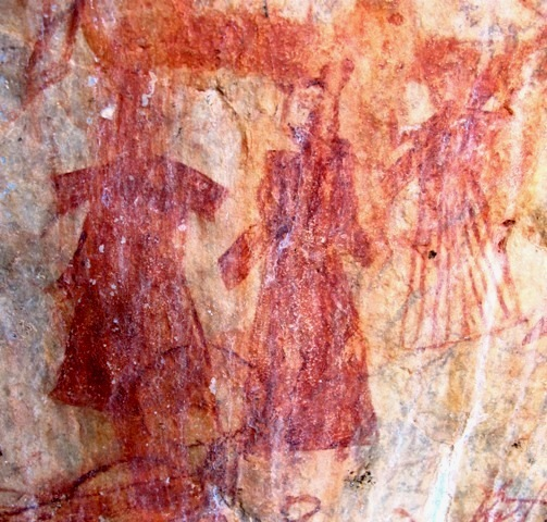Fig. 1. A trio of human figures attired in ankle length robes or caftans gathered at the waist and with relatively short sleeves. These figures and two nearby ones are unlike the depiction of any other anthropomorphic rock art in Upper Tibet. The red ochre figures have undergone considerable wear and ablation of the pigment (each figure is in the vicinity of 10 cm in height). Moreover, the composition is partially obscured by subsequent pigment applications and the running of pigment from adjacent pictographs. As for the age, I shall tentatively attribute it to the imperial period (circa 630–850 CE). Note the line drawing of a yak (horns visible on bottom left corner) superimposed on the composition at a later date.