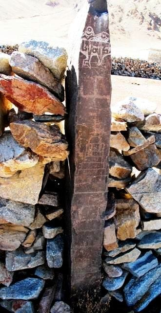 Fig. 7. On the top of the east face of this pillar (1.5 m in height) are the first three letters of the mani mantra below which a primitive or folk-style swastika (arms are much shorter than the central cross) was carved. In a more inferior position are two engraved chortens. The incomplete mani inscription was chiseled using an entirely different technique and exhibits much less wear and re-patination than the other carvings on the pillar. This physical evidence clearly indicates that the inscription was made more recently. Lone chortens and swastikas are found on walled-in pillars from other sites in the region as well. Nevertheless, the carving of such stelae was not common (for other examples, see Antiquities of Zhang Zhung: www.thlib.org/bellezza).