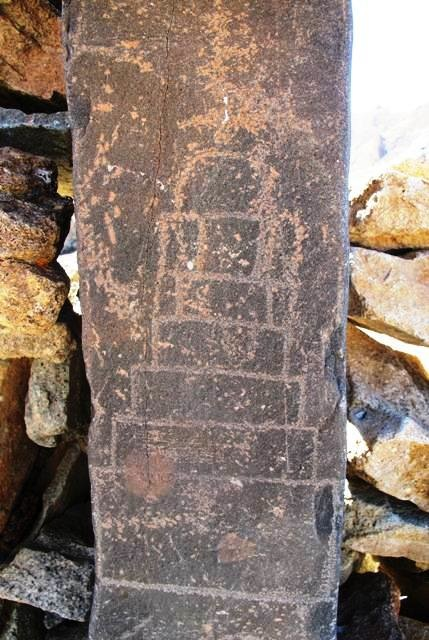 Fig. 8. A close-up of the upper chorten on the pillar reveals more complexity. It is now composed of five sharply incised graduated tiers, which sit on a tall plinth and are topped by a small semi-circular bumpa. The bumpa appears to be surmounted by a segmented spire, which is more heavily patinated and carved in a different manner (using a pecking technique). In fact, this spire, and the bumpa and two of the tiers below it appear to constitute an older and cruder petroglyph. The remainder of the current one was almost certainly added on later using more sophisticated cutting tools. The relative degree of physical wear indicates that possibly centuries separate the creation and recreation of this petroglyph. On the basis of the style and carving technique, the earlier part of the upper chorten, lower chorten (with its three crude tiers and bumpa) and swastika can probably be attributed to the early historic period (650–1000 CE). The more recent portion of the upper chorten dates to the vestigial period (1000–1250 CE) or perhaps even later. The clockwise orientation of the swastika may possibly indicate a Buddhist identity for it and the other carvings as well.