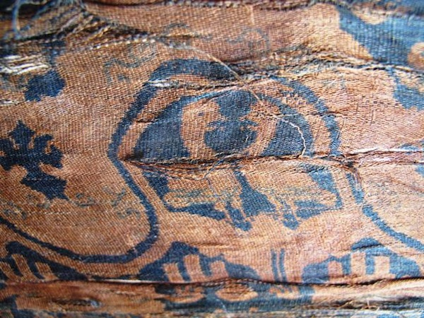 Fig. 2.  A close-up view of confronted waterfowl woven in the Gurgyam silk. What appears to be a pair of ducks or geese stand within wave and floral-like purfle. These motifs are beige in color while the ground is a rich indigo blue.
