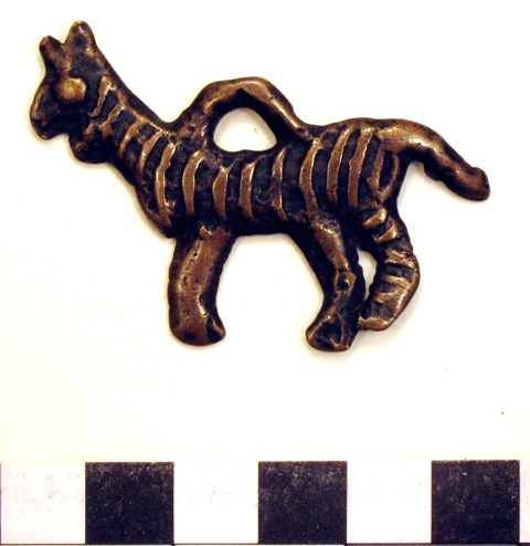 Fig. 11. A copper alloy tiger talisman designed to be hung from the body, early historic period or vestigial period. Tiger thokchas are not particularly common.  This specimen has a rather cartoonish character. Private collection, photograph by author.