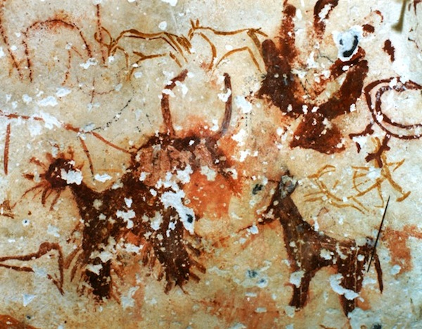 Fig. 1. This is an excellent example of an ancient palimpsest, eastern Changthang. Three animals created by thickly applying blood-red ochre onto a cave wall partially obscure older hunting scenes and other zoomorphic art.