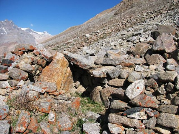 Fig. 14. The subterranean rear/north wall (to the right of the triangular boulder) and west wall (to the left of the the triangular boulder) of DK13. It was common for the outer walls of Upper Tibetan corbelled structures to integrate naturally occurring boulders. An in situ bridging stone resting on the triangular boulder and a corbel (just in front of the bridging stone) are visible.