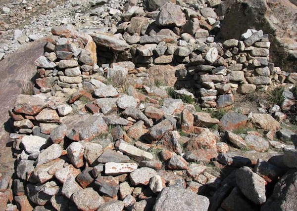 Fig. 15. The rear or upper wall of DK13 integrating large boulders (in the background) and the almost leveled wall dividing the upper and lower tiers of the structure (in the foreground).