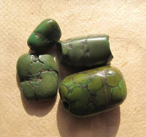 Fig. 19. On close inspection at least two types of green turquoise can be seen in this photograph. The three emerald-green beads with a furrowed surface are of one kind and the lighter green bead with the jigsaw matrix is another kind (bottom right of image). These specimens are also antique variants.