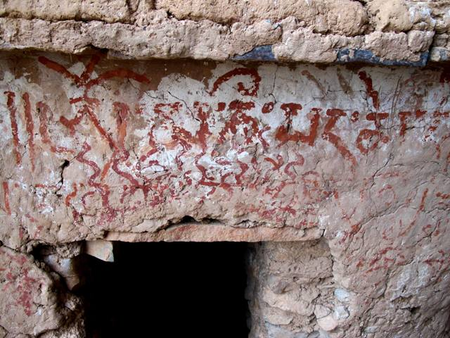 Fig. 10. A mani mantra written in red ochre. This inscription is of significant age (probably 1000–1400 CE), as indicated by the reverse i vowel sign inscribed above the letter na. Also note the wear. The mantra obscures other pigment applications, illustrating its adventitious placement on the chorten. Below the mani mantra is the entranceway to the interior of the chorten. This entranceway has a stone slab lintel.