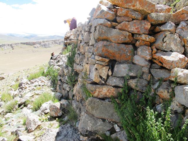 Fig. 28. The forward revetment and wall of the ostensible building. Note the orange climax lichen clinging to the stones. In the background two members of my team take measurements.