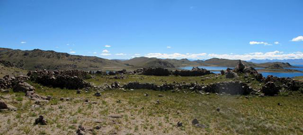 Fig. 7. In the foreground is the wall that bisects the main structure into two equal parts. On the south (right) wall there is a shrine with prayer flags. On the extreme right side of the image, a promontory terminating in a conical formation is visible. This is Nying Do (sNying-do: Heart Headland), a landform thought to have been instrumental in Guru Rinpoche's subjugation of the sacred lake and her mountain mate in the 8th century CE. At Nying Do there is a large cairn, as well as traces of around ten groups of structures, once an extensive residential site. According to local lore, these are the remains of an ancient Bon 'monastery'.