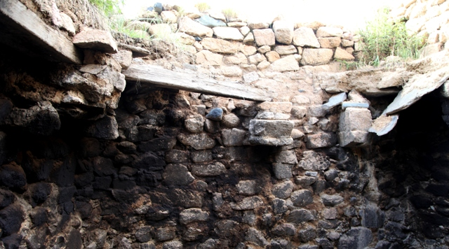 Fig. 10. The interior of the same room pictured in fig. 9. Note the massive stone corbels jutting out from the walls, upon which rest roof members oriented diagonally to them. The two bridging members running along the walls on the left are made of wood, while the one running along the right corner is made of stone in the archaic style of construction. Above the roofline a parapet wall is visible, a typical feature of archaic residences in Upper Tibet as well.