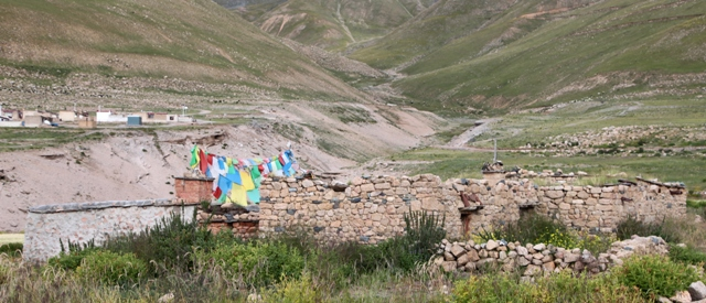 Fig. 15. The east complex of old Kyisum village. The current Kyisum Labrang is surmounted by the red cubic shrine (btsan-khang) and prayer flags. Note the houses of the new planned village in the background.