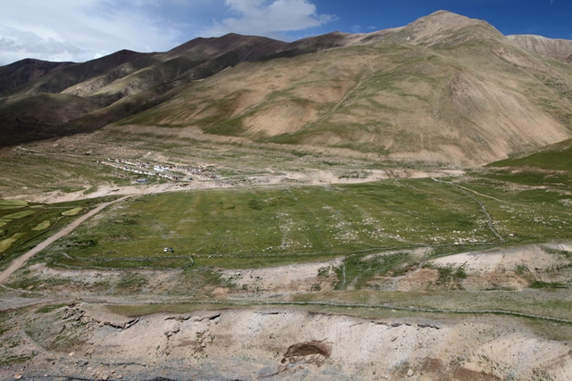 Figure. 3. The large sloping bench in the foreground is believed to have been farmed at one time. Its geomorphological characteristics support this attribution. This forsaken agricultural zone is flanked by Kyisum's two main streams, neither of which is still of sufficient volume to water it. On the left side of the image, cultivated fields of the viable agricultural sector are visible, on the opposite side of the road. In the background, the new planned village of Kyisum can be seen.