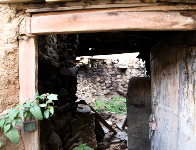 Fig. 9. An entranceway with a wooden doorframe in one of the rooms of the original Kyisum Labrang. This doorframe was once tinted red with ochre. This structure stands in the middle of the old Bon estate. Presumably, it formed part of the heart of the old religious estate, explaining its larger doorway, higher ceiling and more commodious interior. In Buddhist and Bon temples built in Upper Tibet after 1000 CE, large doorways and high ceilings are commonplace.