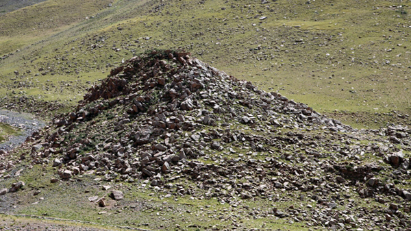 Fig. 15. The conical mount of Gyangpai Tsuk Dzong (4755 m elevation). The brownish zone on the left side (southeast) of the steep hill is comprised of scattered defensive walls.