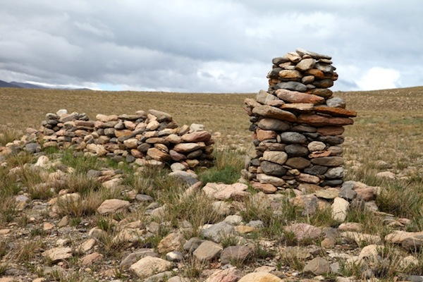 Fig. 18. A rudimentary shrine and wall, Lake Vanguard sector, Bell Island. The form of this shrine is immediately recognizable to modern-day Tibetans, for their shrines still take the same shape. It consists of a square base, overlapping middle courses and a smaller top section. Originally, the topmost portion may have been a spherical structure (bum-pa), a fundamental element of Tibetan chorten construction since the 7th century CE. Note the orange climax lichen growing on the shrine.