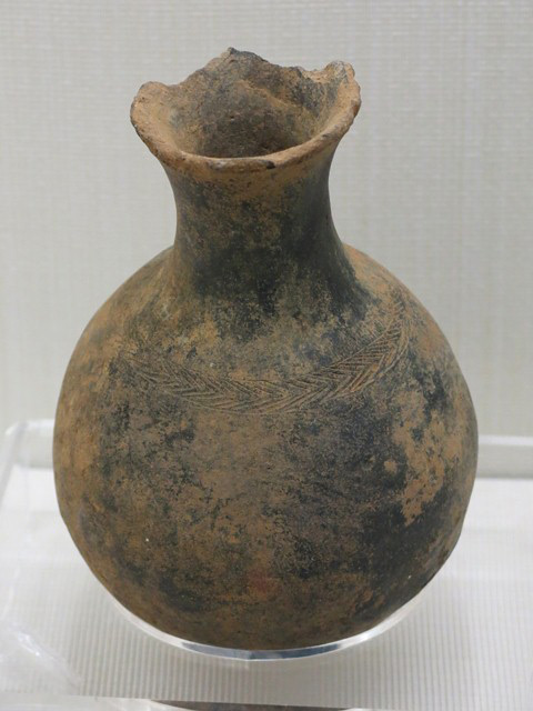 Fig. 104. Burnished dark-gray ware globular jar, with medium-length neck and flaring rim. A band of incised chevrons rings the shoulder of the vessel. Pre-Imperial period. Tibet Museum collection.