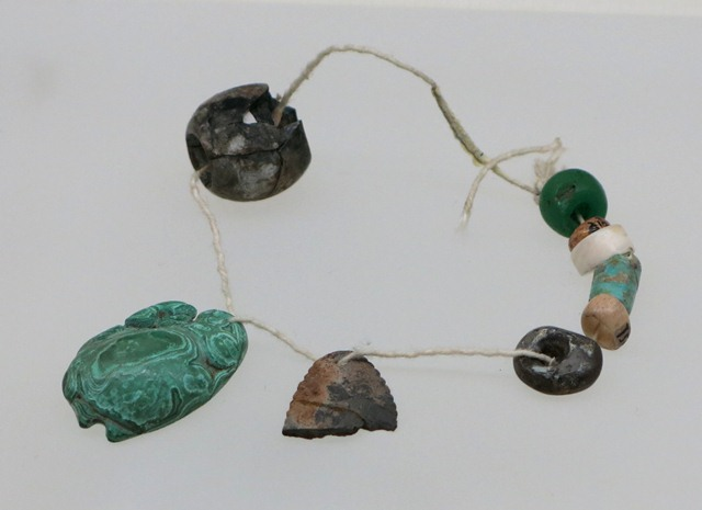 Fig. 44. Stone pendant of malachite, a cylindrical bead of turquoise (?) and beads of other substances, Kharub, Chamdo. Middle or Late Phase of Neolithic (5300–4000 BP). Tibet Museum collection.