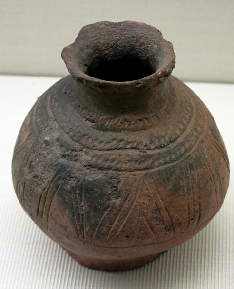 Fig. 54. Globular reddish-buff ware jar with constricted neck, flared rim and flat base. Incised triangles cover the body of the vessel and a lineal motif was stamped into the shoulder and neck of the vessel. Kharub, Chamdo, Middle or Late phase of the Neolithic (5300–4000 BP). Tibet Museum collection.