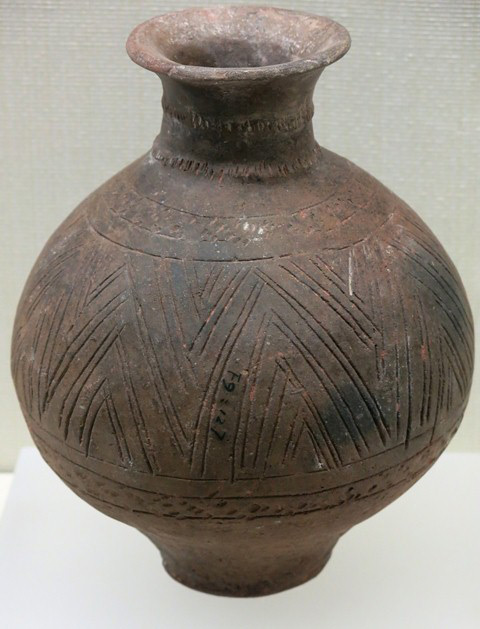 Fig. 55. A globular jar of reddish-buff ware with truncated lower section and flat base. At the bottom of the body is a band of punctates. Incised geometric designs consisting of graduated triangles are found on the body, while rows of lines were graved on the shoulder and relatively long neck of the jar. The lip of the jar is somewhat flattened. Kharub, Chamdo, Middle or Late phase of the Neolithic (5300–4000 BP). Tibet Museum collection.