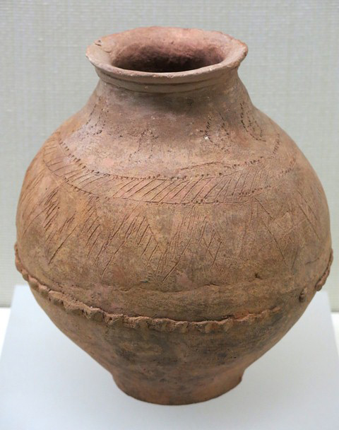 Fig. 56. A short-necked bulbous jar of yellowish-brown ware with flat base. The neck merges