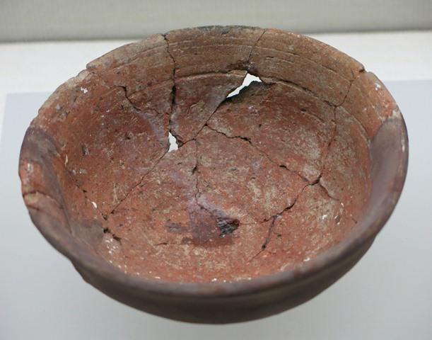 Fig. 58. A red ware bowl with a slightly flaring rim. Note the incised lines encircling the top portion of the vessel. The dark area in the foreground is a reconstructed portion of the vessel. Kharub, Chamdo, Middle or Late phase of the Neolithic (5300–4000 BP). Tibet Museum collection.
