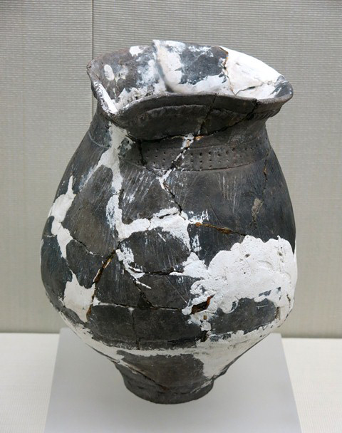 Fig. 66. An ellipsoidal jar of dark-gray ware, with tapering lower body, flat base, flaring lip, and open spout. Decorations were made through incising and with punctates. Kharub, Chamdo, Middle or Late phase of the Neolithic (5300–4000 BP). Tibet Museum collection.