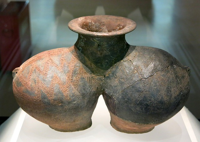 Fig. 67. A highly unusual double-bodied jar of red ware, with two zigzag bands of incised decorations around the bodies, flat bases, short neck, and broad, flattened rim. Note the lugs on the two sides of the vessel. This jar with its ellipsoidal bodies was mostly covered with black (manganese oxide) and red (iron oxide) paints. Kharub, Chamdo, Middle or Late phase of the Neolithic (5300–4000 BP). Tibet Museum collection.