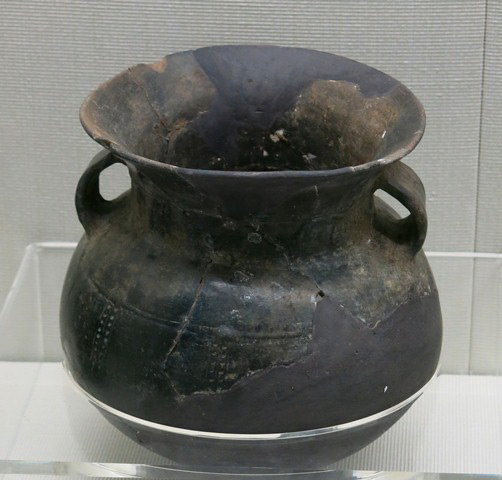 Fig. 78. A burnished globular jar of dark-gray ware, with wide neck, flaring lip and two lug handles. The body is adorned by punctates aligned vertically. Note the molded bead encircling the middle of the body. Chugong, Lhasa, late Neolithic (4000–3500 BP). Tibet Museum collection.
