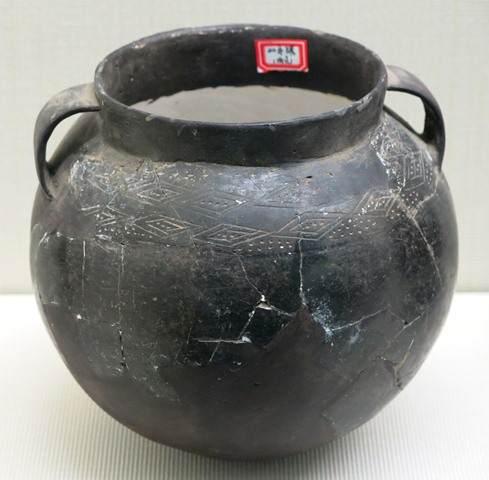 Fig. 82. A burnished dark-gray ware globular jar, with a very short, straight neck, and two strap handles set high on the shoulder and neck. Along the shoulder are two incised bands of triangles and punctates. Chugong, Lhasa, late Neolithic (4000–3500 BP). Tibet Museum collection.