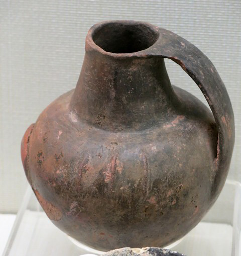 "Fig. 97. Globular jar of burnished reddish-buff ware, with long, tapering conoidal neck, and large strap handle attached to the rim and the middle of the body of the vessel. Found in a ""Xiangbei"" stone-chambered tomb, Gonjo county, Chamdo prefecture. Pre-Imperial period. Tibet Museum collection."