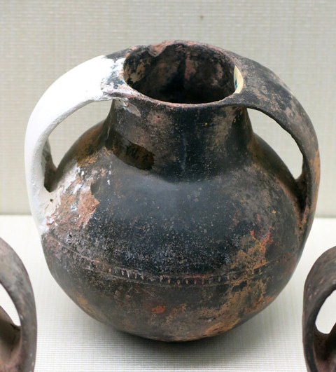 "Fig. 99. Globular jar of reddish-buff ware with two large strap handles attached to the rim. A punctated ribbon encircles the middle of the vessel. Found in a ""Xiangbei"" stone-chambered tomb, Gonjo county, Chamdo prefecture. Pre-Imperial period. Tibet Museum collection."