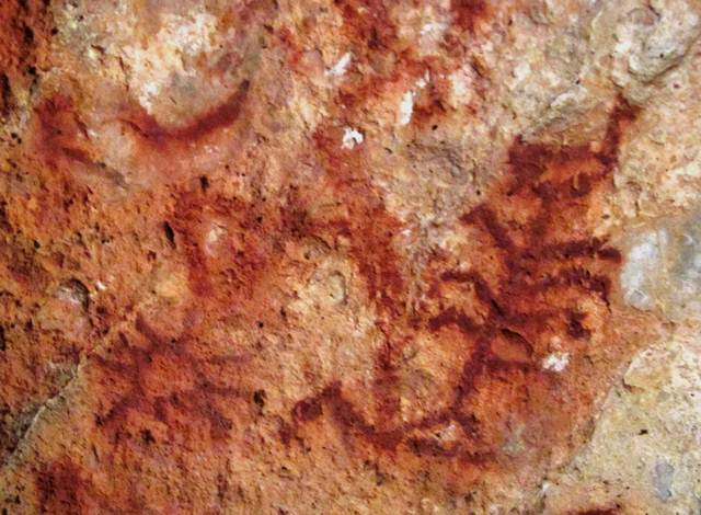Fig. 82. A portion of a panel of red ochre pictographs at Lhari Drakphuk, Upper Tibet. Clearly visible in a deep red ochre hue is a sunburst, crescent moon and tree. Protohistoric period.