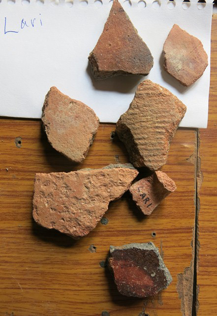 "Fig. 8. Smooth-walled and cord-marked redware from the village of Lari. Note what appears to be part of a handle marked ""Lari"". Some of these ceramics may have been deposited in tombs."