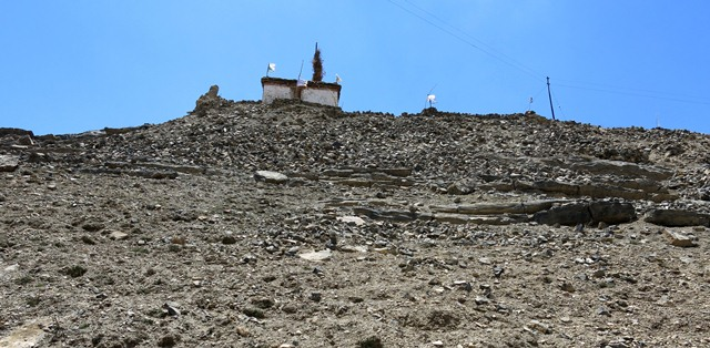 Fig. 12. The northeast side of the hill at Kharteng. Note the lhatho shrine and chapel on the summit and the rubble strewn slopes below.