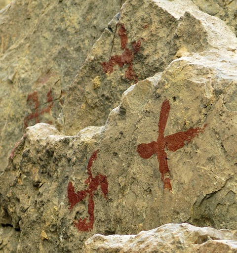 Fig. 25.6. Three red ochre swastikas and cruciform painted on a cliff face near the rock ceiling, Kubum.