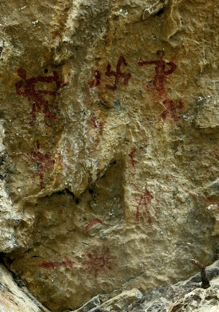 Fig. 26.2. One of the rock faces at Thonsadrak 1. On the upper portion of the panel are two anthropomorphs flanking a swastika and crescent moon (partially effaced). Below the anthropomorph on the right is another swastika. On the lower part of the panel is a sunburst and horizontal line.