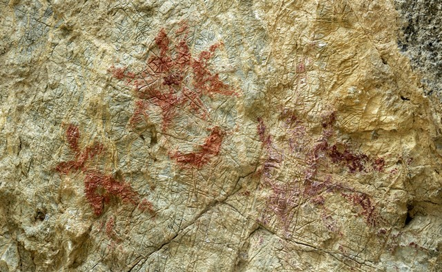 Fig. 26.5. Pictographs on the rock face of Thonsadrak 2. From left to right: anthropomorph, sunburst, crescent moon, and sunburst. The darker red ochre sunburst on the right was made on a different occasion. Nevertheless, these respective compositions complement one another.