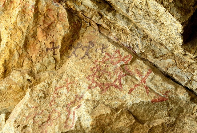 Fig. 28.10. Pictographs on west wall of Sinmo Khadang situated above rock face in fig. 28.3. There is a large sunburst in the middle of the image. Above it is a pair of anthropomorphs flanked by swastikas forming a single composition.