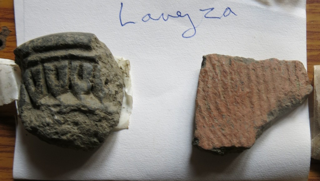 Fig. 35. Two sherds of pottery collected by the SRAHS in Langdza. The cord-marked buffware fragment on the right is of a type that was used in mortuary rites (non-funerary functions for these ceramics may also be indicated). The thick-walled greyware fragment on the left with its stamped or molded decorations is of a type that is probably of much more recent manufacture.