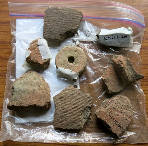 Fig. 50. Various ceramic fragments and ceramic spindle whorl collected around Chichim village. Some of these sherds may be from mortuary vessels. The whorl may have come from the grave of a female.