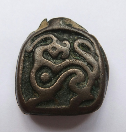 Fig. 8.  The other side of the thokcha in fig. 7. This side of the object is embossed with what appears to be either a dragon or fantastic creature. Photo courtesy of Carol Yong.
