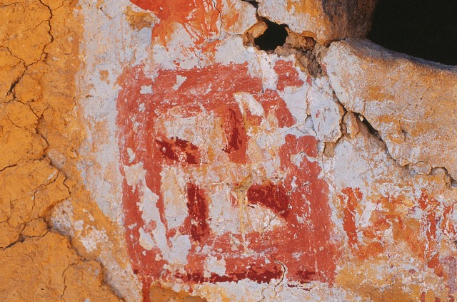 Fig. 53. A counterclockwise swastika painted in white and two shades of red ochre beside the primal syllable A. This painting is found on the wall of a ruined hermitage in the western Changthang, one associated with the great Dzokchen practitioner known as Tapihritsa (Ta pi hri tsa).