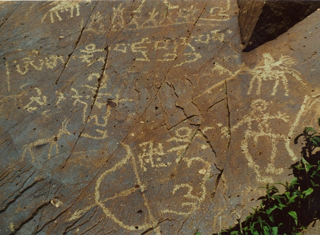 Fig. 60. Buddhist rock art and inscriptions, central Changthang. Vestigial period. The upper inscription is the vajra mantra for Guru Rinpoche. Higher up on the rock face is another Buddhist composition which I have treated elsewhere. Although the swastika accompanying the syllable hum' and bow and arrow faces counterclockwise, it is a Buddhist symbol. The detailed but clumsily executed horseman and standing anthropomorphic figure typify the decadence of Upper Tibetan rock art in the final period of production.