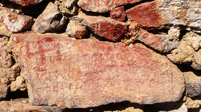Fig. 71. Clockwise swastika painted over part of the Yungdrung Bon mantra for the god of boundless light, Shenlha Ökar, western Changthang. These red ochre inditements occur on the main foundation stone of a ruined hermitage (also see figs. 53–55). Vestigial period.