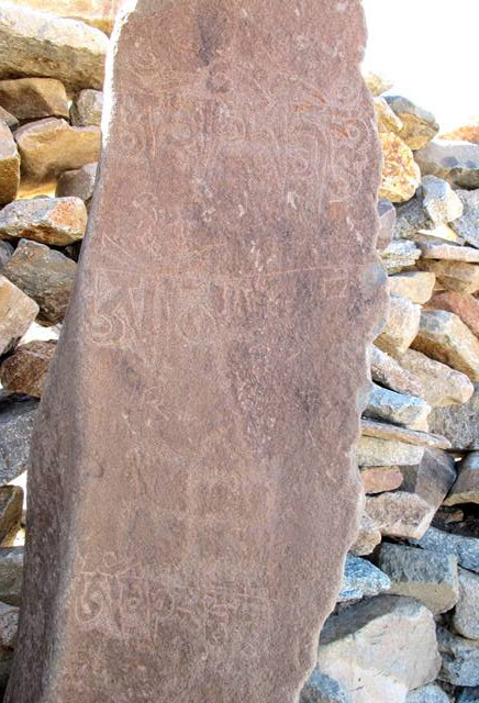 Fig. 79. Counterclockwise swastika and more recent mani mantras added to a prehistoric funerary ritual pillar, northwestern Tibet.
