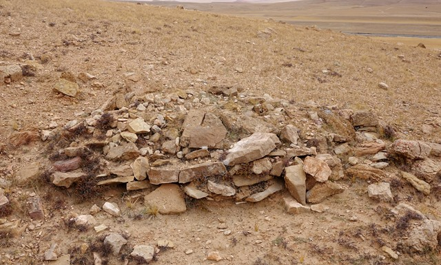 Fig. 27. A tomb comprised of several vertical courses of masonry (FS5). Perched on the edge of a gully, this tomb was exposed some years earlier by running water. Human bones are no longer visible on the surface of the structure.