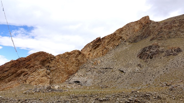 Fig. 2. The shrine complex on a bench (foreground) and ruins of the upper residential complex on slope paralleling the middle reaches of the orange rock formation, a tall rib of limestone. The dark-colored outcrop in the middle of the slope (right side of photograph) also hosted residential structures.