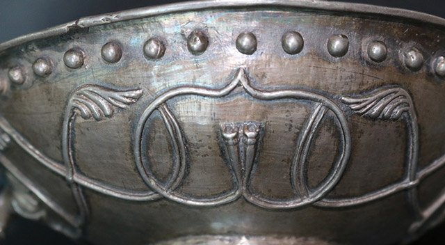A close-up view of the decorative pattern on the silver bowl, consisting of interconnected ridges forming an inverted heart-shaped field, ...